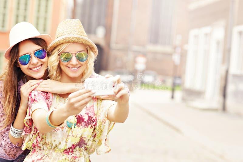Dwa szczęśliwego dziewczyna przyjaciela bierze selfie obrazy royalty free