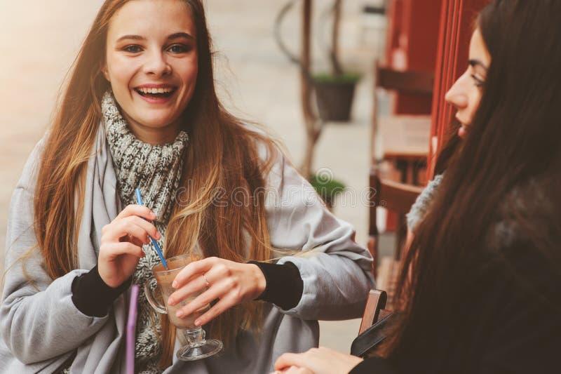 Dwa szczęśliwego dziewczyna przyjaciela opowiada kawę w jesieni mieście w kawiarni i pije obraz stock