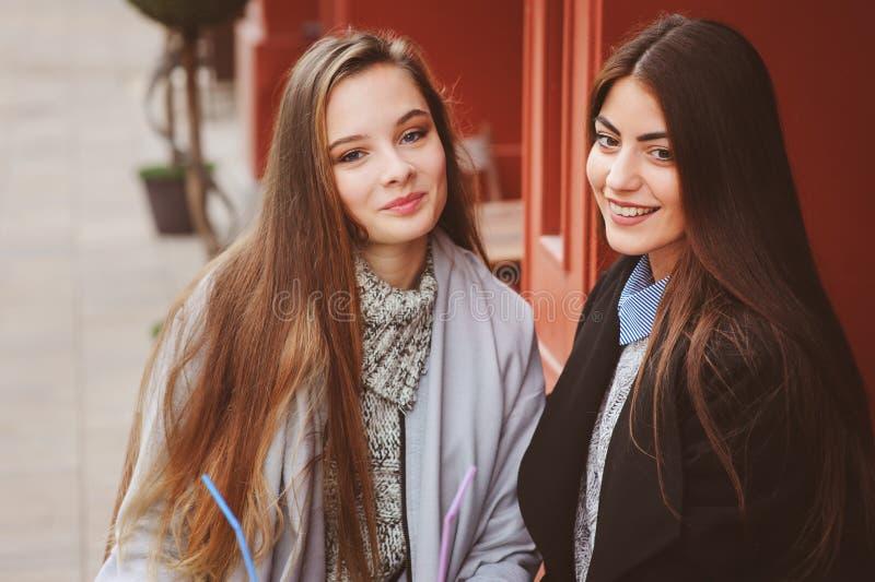 Dwa szczęśliwego dziewczyna przyjaciela opowiada kawę w jesieni mieście w kawiarni i pije obraz royalty free