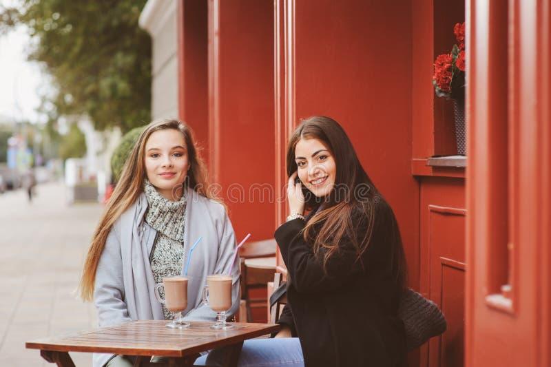 Dwa szczęśliwego dziewczyna przyjaciela opowiada kawę w jesieni mieście w kawiarni i pije fotografia stock