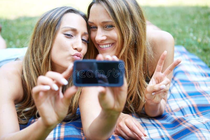 Dwa szczęśliwego kobieta przyjaciela dzieli ogólnospołecznych środki obrazy royalty free