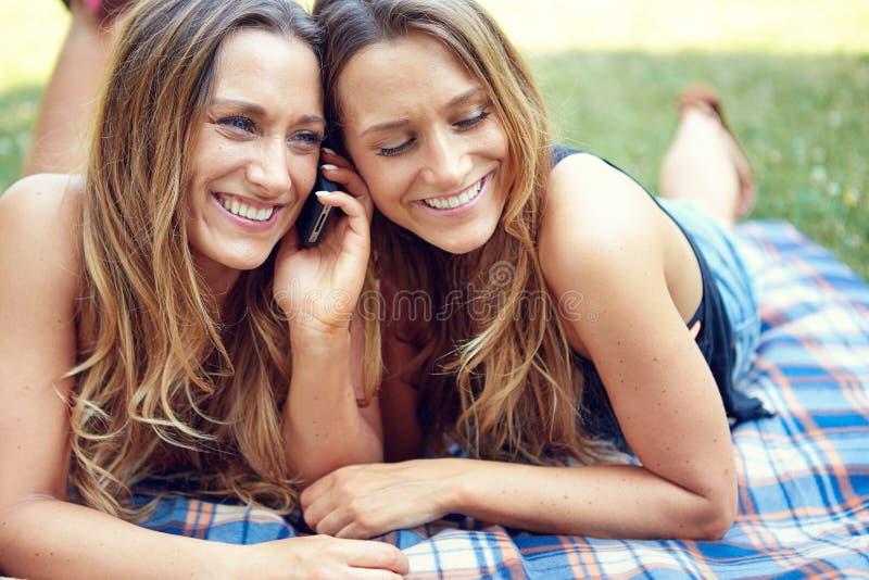 Dwa szczęśliwego kobieta przyjaciela dzieli ogólnospołecznych środki w a zdjęcie royalty free