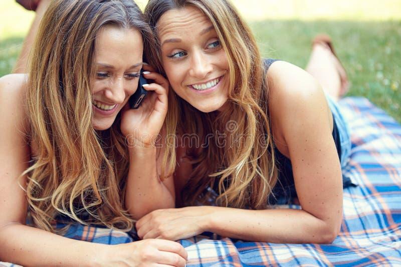 Dwa szczęśliwego kobieta przyjaciela dzieli ogólnospołecznych środki w a fotografia stock