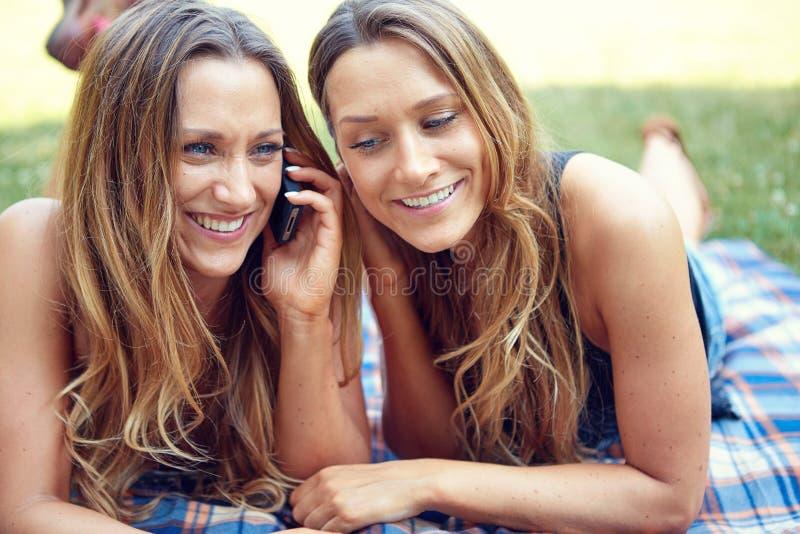 Dwa szczęśliwego kobieta przyjaciela dzieli ogólnospołecznych środki w a zdjęcie stock
