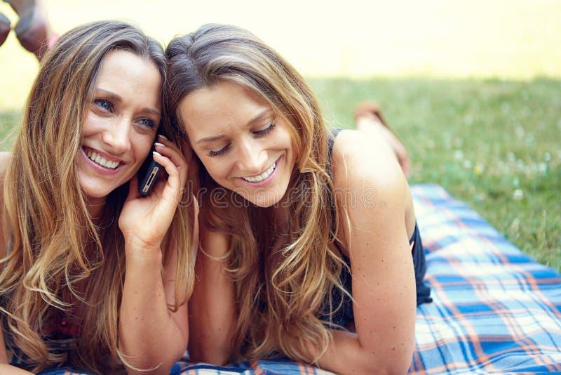 Dwa szczęśliwego kobieta przyjaciela dzieli ogólnospołecznych środki w a zdjęcia stock