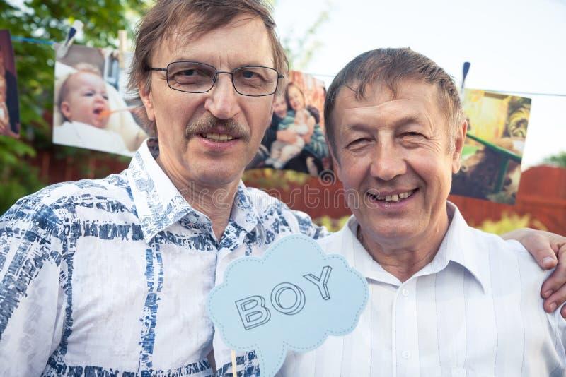 Dwa szczęśliwego obejmowania uśmiecha się starszych mężczyzna stoi wpólnie podczas przyjęcia urodzinowego z chłopiec znakiem obraz stock
