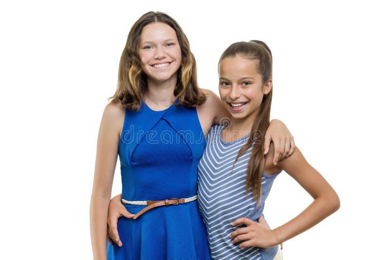 Dwa szczęśliwego pięknego młoda dziewczyna przyjaciela obejmuje, z doskonalić białym uśmiechem, odizolowywającym na białym tle zdjęcia stock