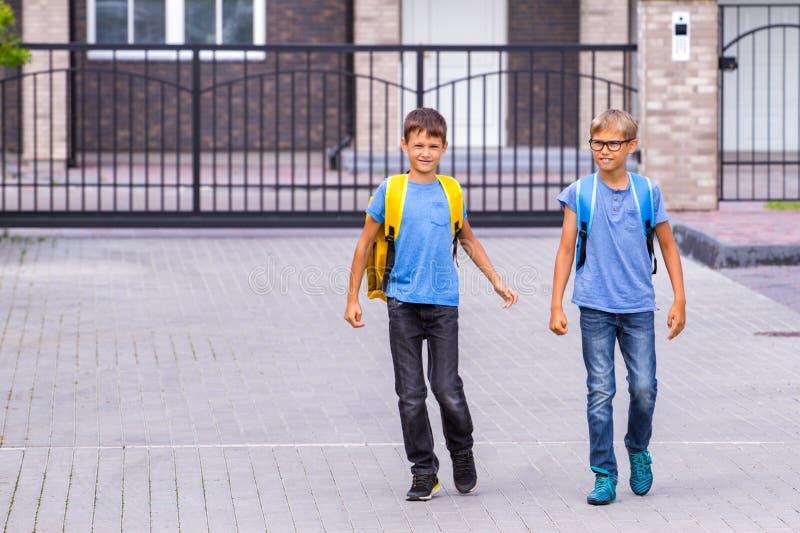 Dwa szczęśliwego shoolboys z plecakami iść szkoła w ranku fotografia royalty free