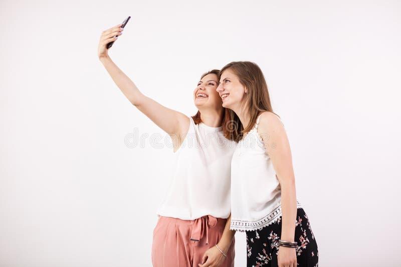 Dwa szczęśliwego wspaniałego młoda kobieta przyjaciela uśmiecha się selfie i bierze obraz stock