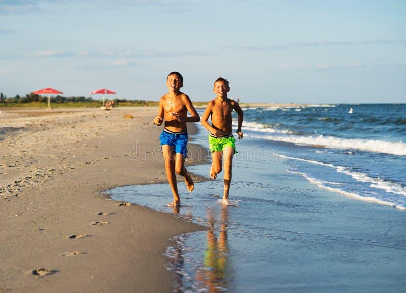 Dwa szczęśliwej chłopiec biega na morzu wyrzucać na brzeg przy latem z nastroszonym ar fotografia royalty free