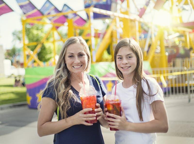 Dwa szczęśliwej dziewczyny cieszy się chłodno napój przy parkiem rozrywki zdjęcia royalty free