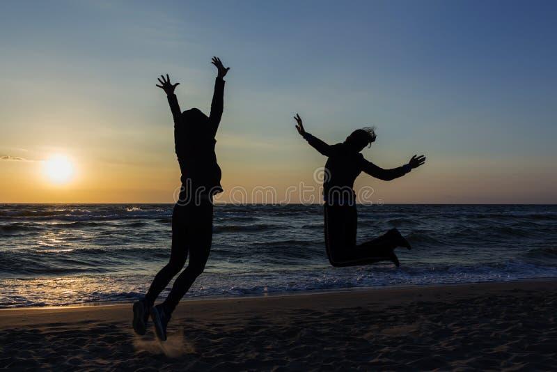 Dwa szczęśliwej dziewczyny ma zabawę i pozycję z nastroszonymi rękami na tle zmierzchu morze obraz stock
