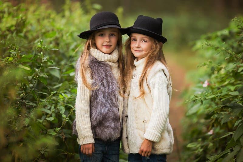 Dwa szczęśliwej dziewczyny równo ubierają: w futerkowych kamizelkach i kapeluszach w lasowych Małych dziewczynach w parku fotografia stock