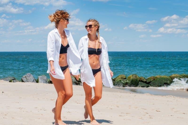 Dwa szczęśliwej dziewczyny w bikini na plaży Najlepsi przyjaciele chodzi na plaży obraz stock