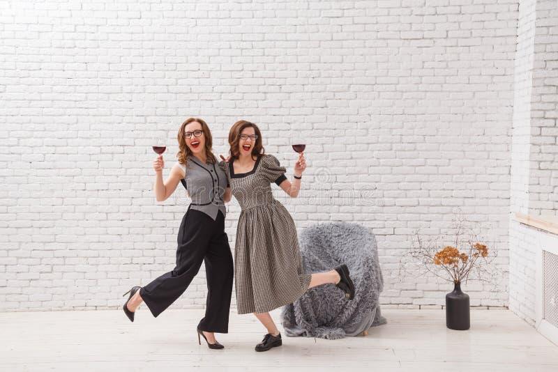 Dwa szczęśliwej kobiety, mieć zabawę i pijący czerwone wino na przyjęciu Modny ubierający z pięknym falistym włosy Na loft bielu zdjęcie stock