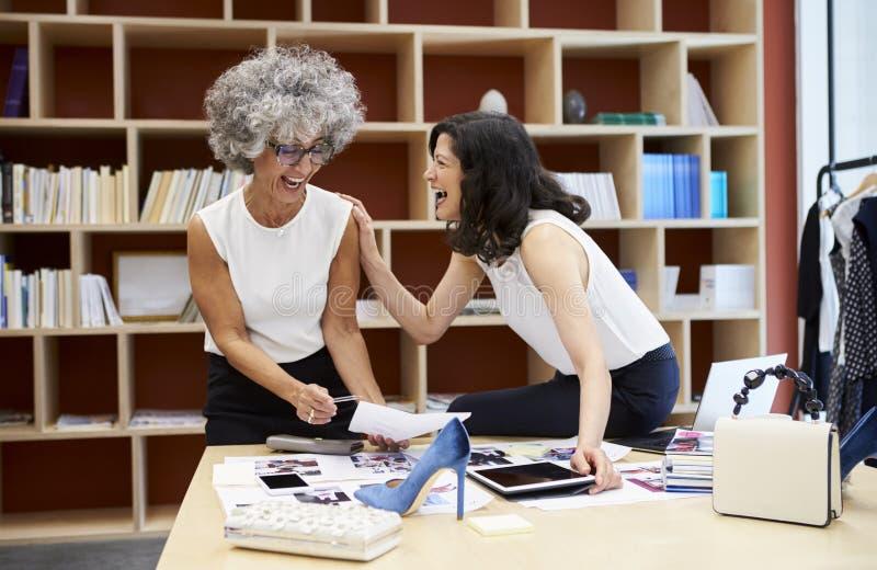 Dwa szczęśliwej kobiety opowiada w kreatywnie medialnym biurze, zamykają up obraz royalty free
