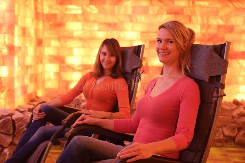 Dwa szczęśliwej kobiety relaksuje w holotherapy solankowym pokoju zdjęcie stock