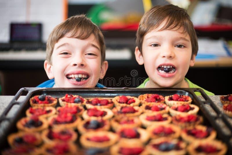 Dwa szczęśliwej młodej chłopiec pomaga z przygotowaniem babeczki zdjęcie stock