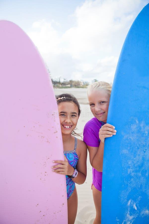 Dwa szczęśliwej młodej dziewczyny trzyma surfboards przy plażą zdjęcie royalty free