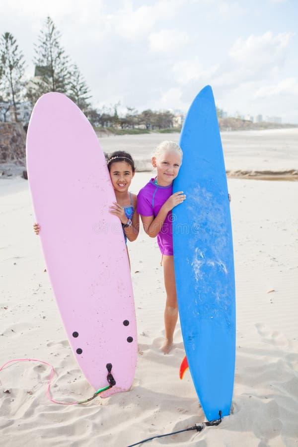 Dwa szczęśliwej młodej dziewczyny trzyma surfboards przy plażą zdjęcia royalty free