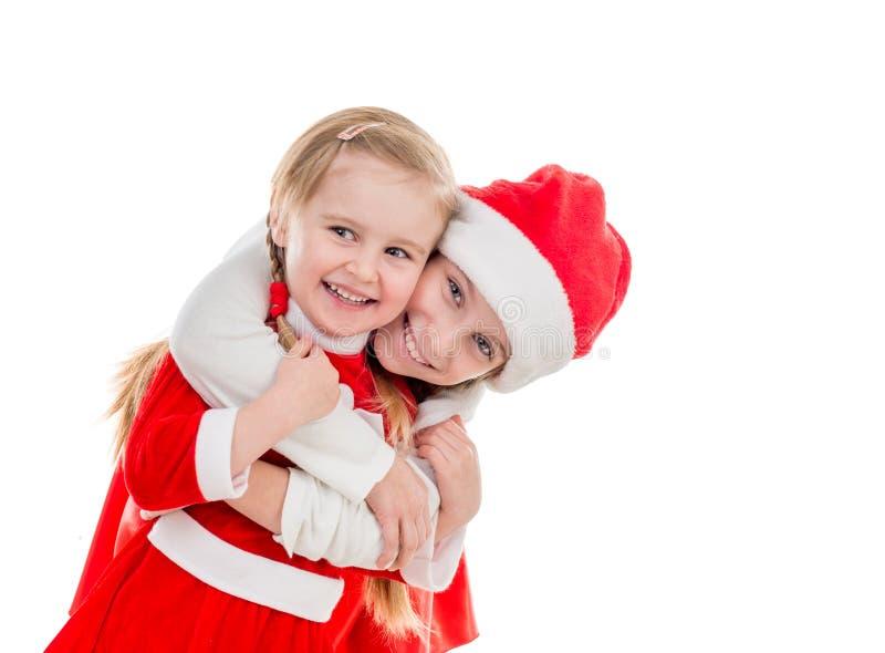 Dwa szczęśliwej małej dziewczynki w Santa nadają się obejmowanie zdjęcia royalty free
