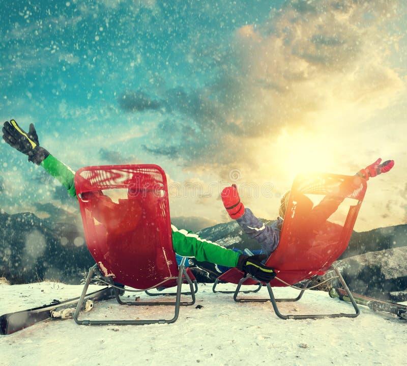 Dwa szczęśliwej narciarki siedzi w bryczce na wierzchołku śnieg mo zdjęcia stock