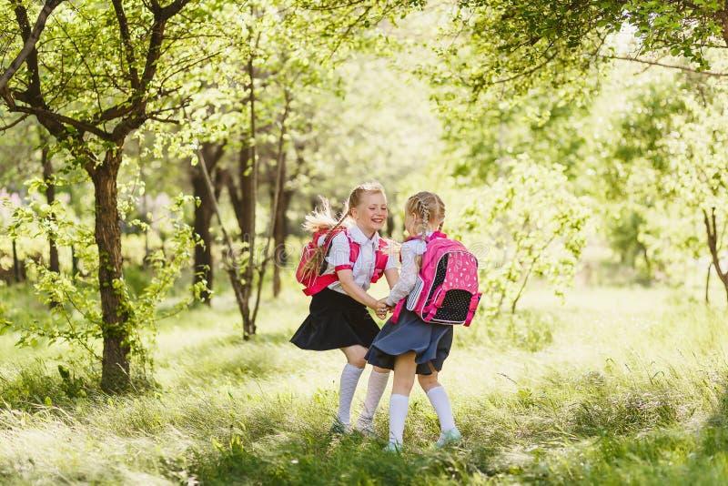 Dwa szczęśliwej szkolnej dziewczyny początkowe klasy outdoors zdjęcia stock