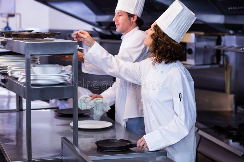 Dwa szefa kuchni pracuje przy rozkaz stacją w kuchni obrazy royalty free