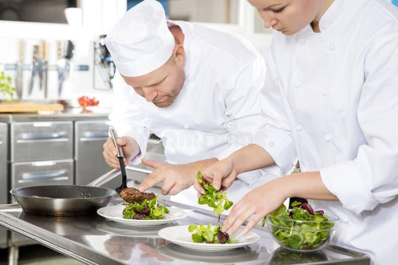 Dwa szefa kuchni przygotowywają stku naczynie przy wyśmienitą restauracją obrazy royalty free