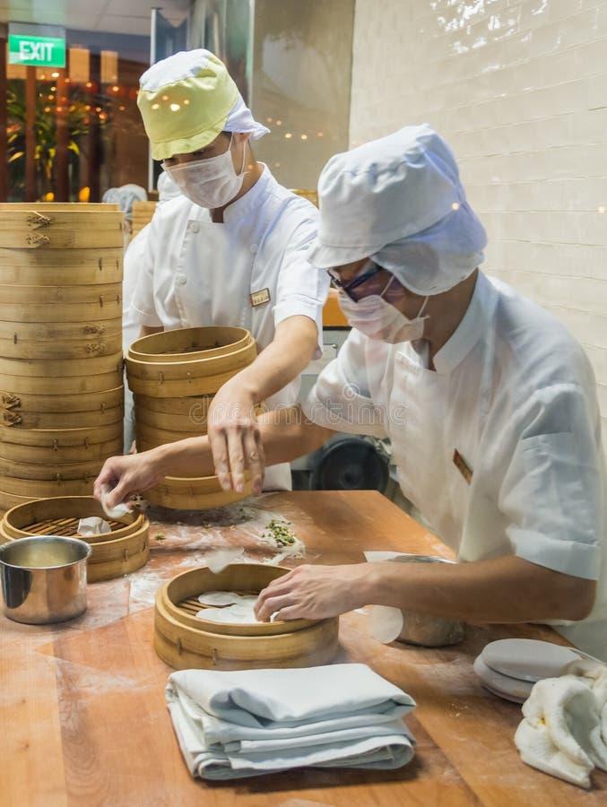 Dwa szefa kuchni w białych mundurach przygotowywa naczynie ciasto w kuchni troszkę, Singapur obraz royalty free