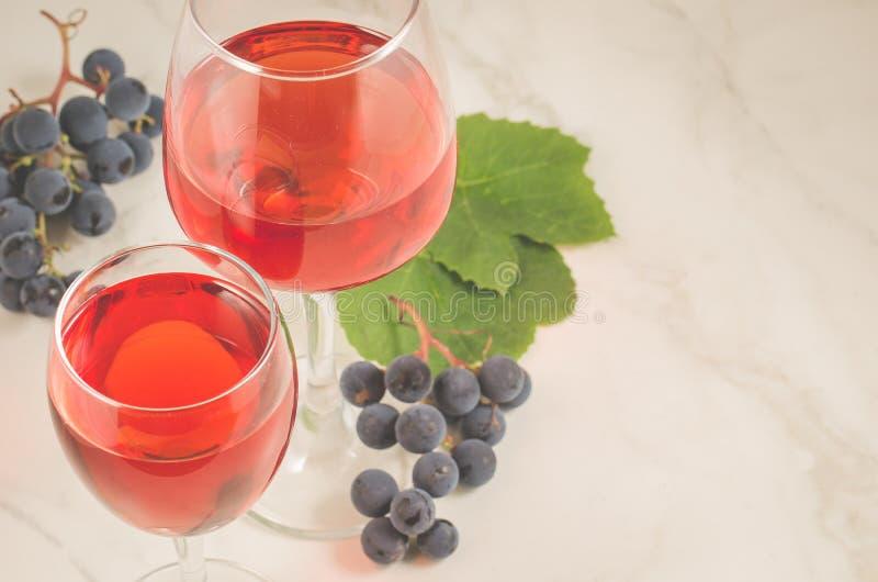 Dwa szkła czerwone wino i winogrono nad czerwonym winem i winogronami na białym marmurowym tle biel/dwa zdjęcia stock