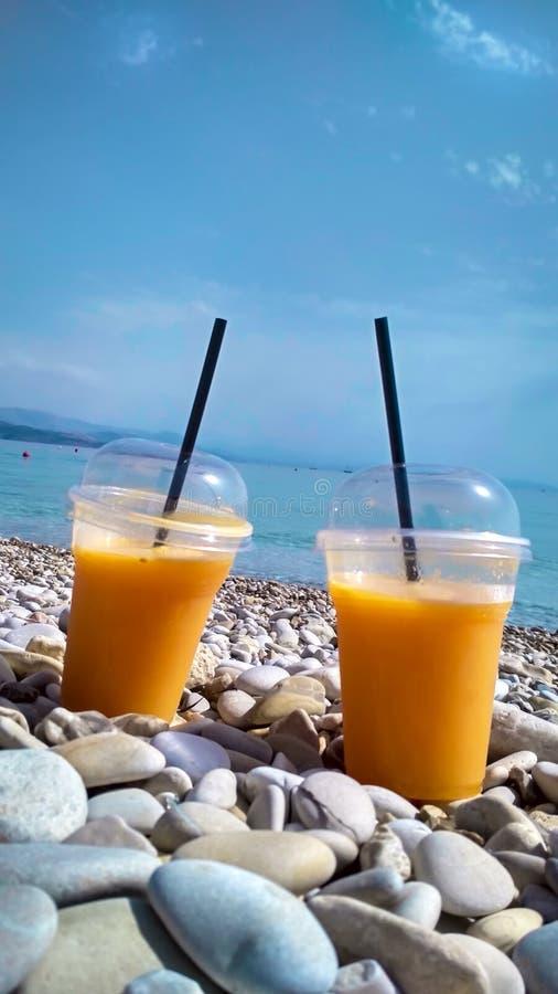 Dwa szkła świeży sok pomarańczowy na otoczak plaży zdjęcie stock