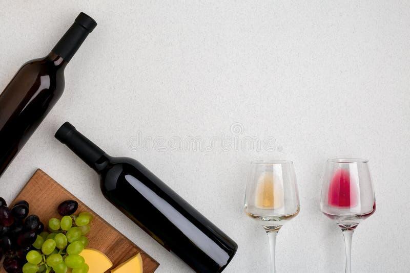 Dwa szkła biel, czerwone wino, ser i winogrona, Odgórny widok fotografia royalty free