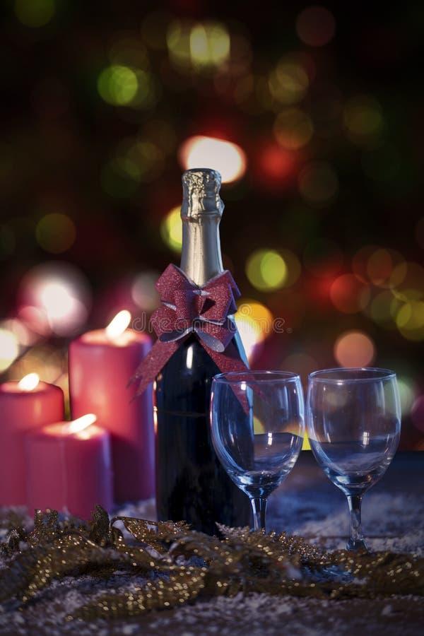 Dwa szkła i szampańskiej butelka z czerwonymi świeczkami fotografia stock