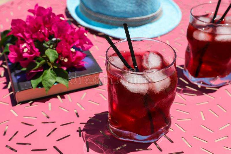 Dwa szkła lato czerwony koktajl z lodem obok książki, sprig Bougainvillea kwitną, błękitny kapelusz na różowią stół zdjęcie royalty free