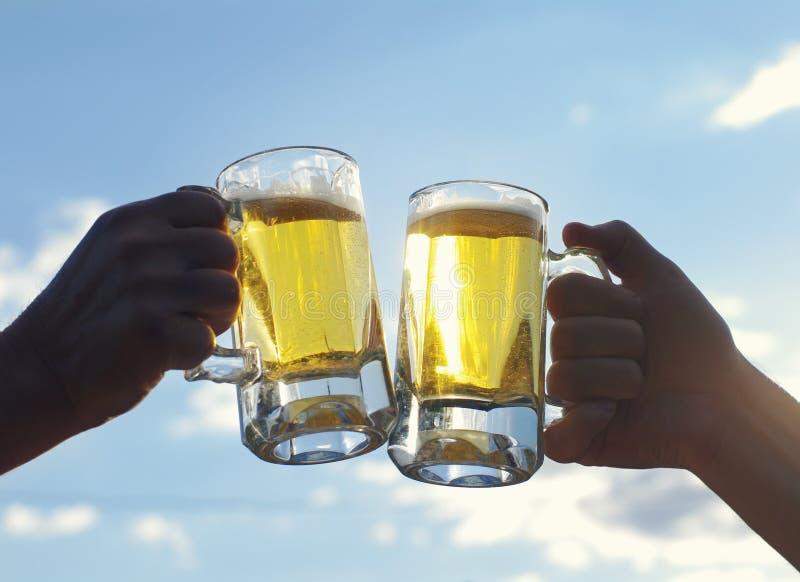 Dwa szkła lekkiego piwa chwyta samiec ręki przeciw niebieskiemu niebu Przyjaciele wznosi toast z pszenicznym piwem zdjęcia stock