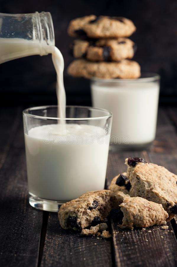 Dwa szkła mleko i ciastka na drewnianym stole szkła mleko nalewał Czarny tło Selekcyjna ostrość fotografia stock