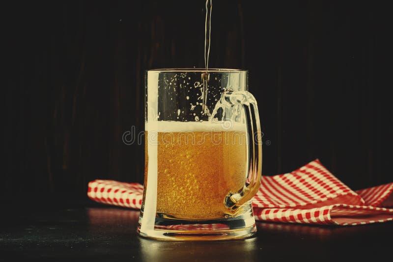 Dwa szkła niemiecki lekki piwo, piwo nalewali w kubek, zmroku bar zdjęcie stock