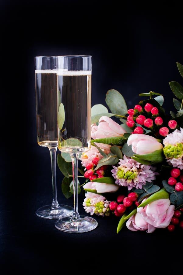 Dwa szkła szampan i bukiet różowi kwiaty obrazy stock