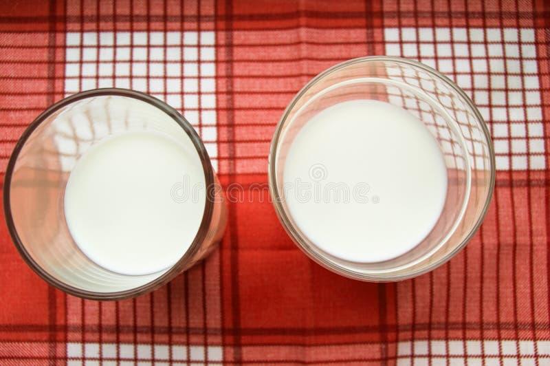 Dwa szk?a mleko stojak na czerwonym w kratk? p??tnie, odg?rny widok obraz royalty free