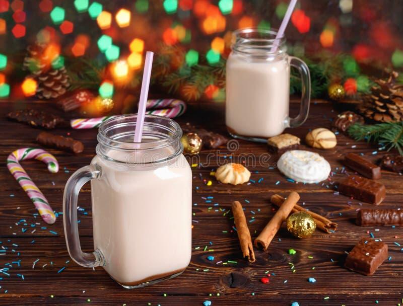 Dwa szklanej fili?anki gor?cy kakao z mlekiem, cynamonem, cukierkami i s?omian? tubk?, zdjęcie stock