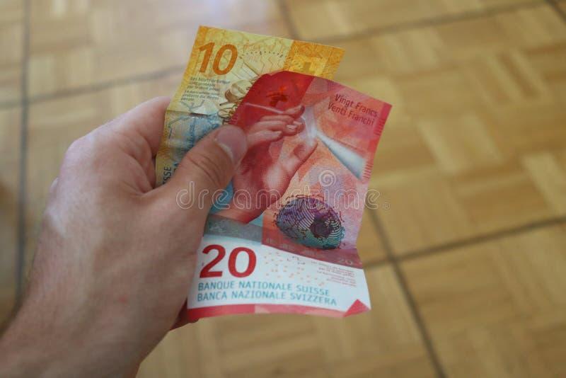 Dwa szwajcarskiego franka banknotu w mężczyzna ręce zdjęcie royalty free