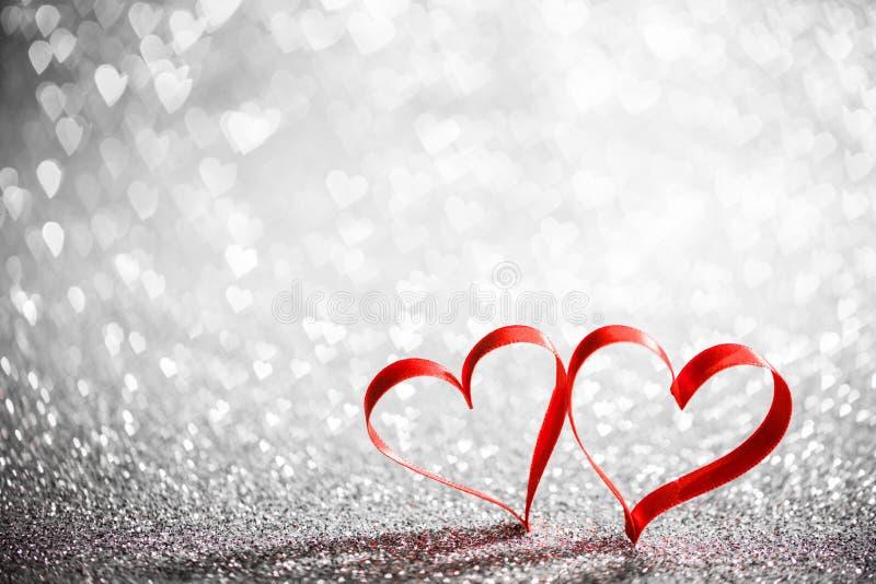 Dwa tasiemkowego serca na rozjarzonym tle zdjęcie royalty free
