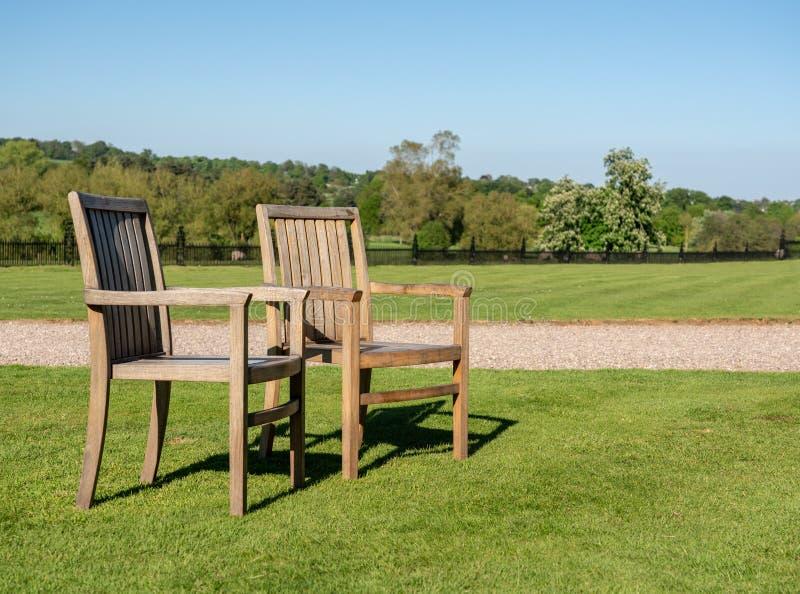 Dwa tekowego krzesła na gazonie w ampuła ogródzie obrazy stock