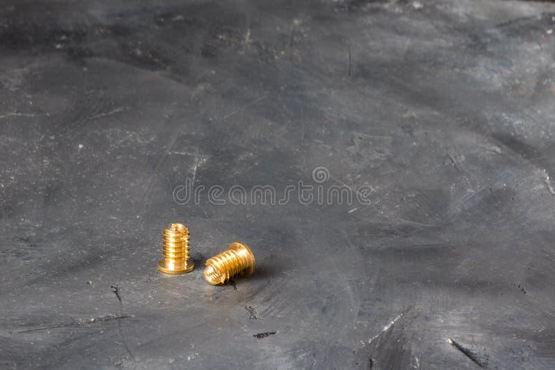 Dwa threaded wszywki uzupełniającej od złocistego colour metalu na chalkboard tle fotografia stock