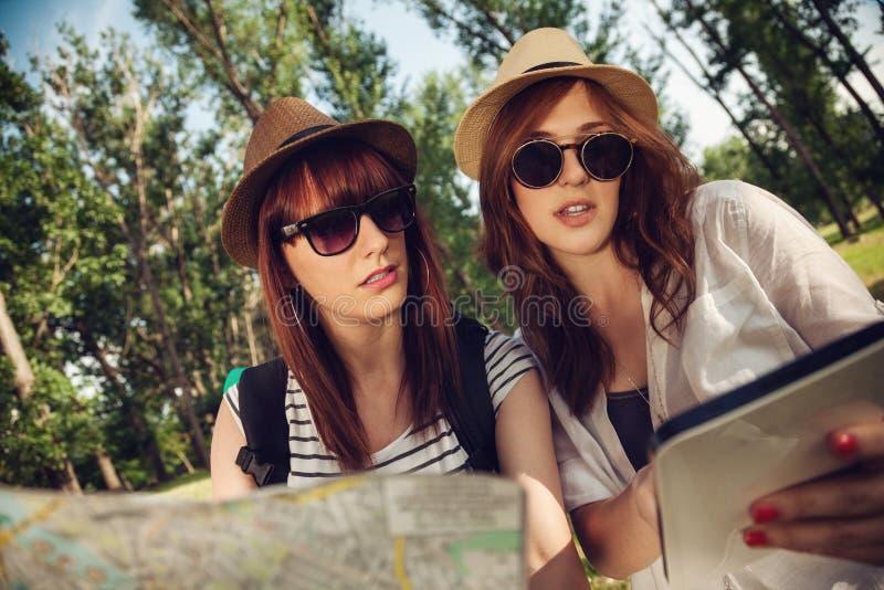 Dwa Turystycznej dziewczyny Używa mapę I Digital pastylkę zdjęcie stock