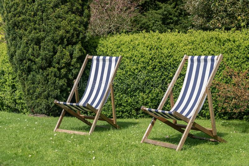 Dwa typowego angielskiego deckchairs na gazonie w ogródzie zdjęcie stock