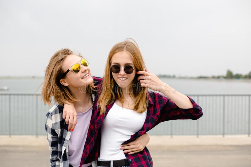 Dwa uśmiechniętego żeńskiego przyjaciela ściska each inny na ulicie Wakacji, wakacje, miłości i przyjaźni pojęcie, zdjęcie royalty free