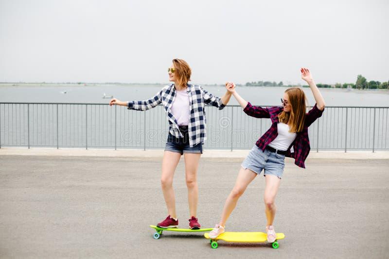 Dwa uśmiechniętego żeńskiego przyjaciela uczy się jeździeckiego longboard z pomagać each inny tła pojęcia ciemny przyjaźni pelika zdjęcie stock