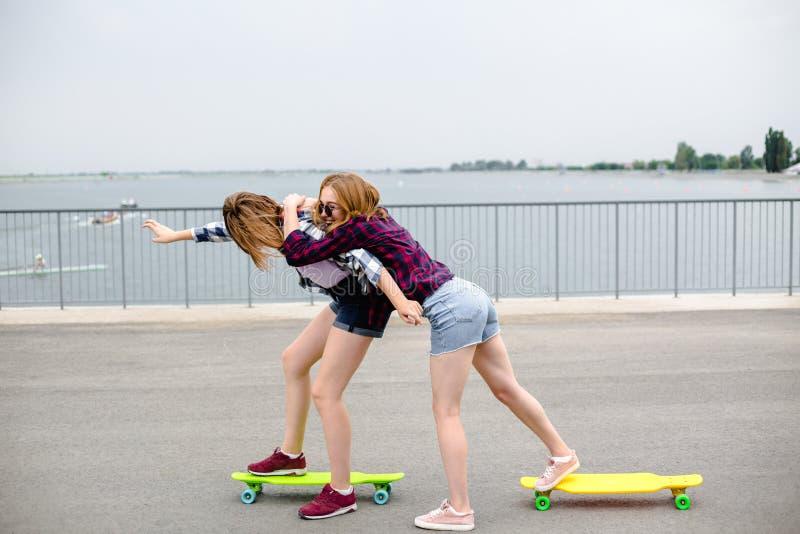 Dwa uśmiechniętego żeńskiego przyjaciela uczy się jeździeckiego longboard z pomagać each inny tła pojęcia ciemny przyjaźni pelika obrazy royalty free